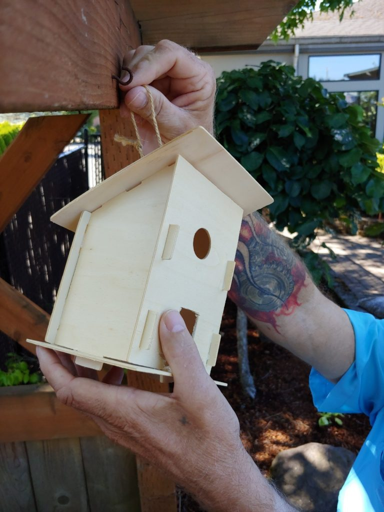 Image of arms and hands only hanging a bird house