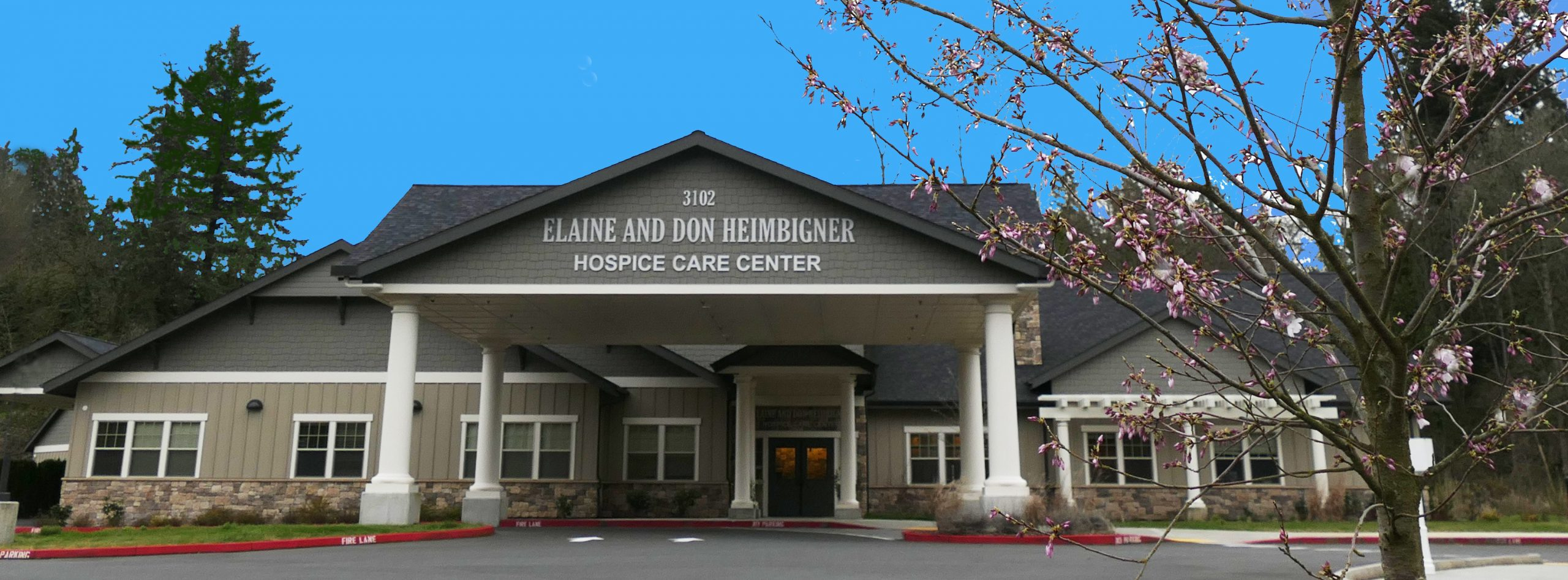 Front entrance of the Elaine and Don Heimbigner Hospice Care Center with a blue sky and a blooming dogwood tree
