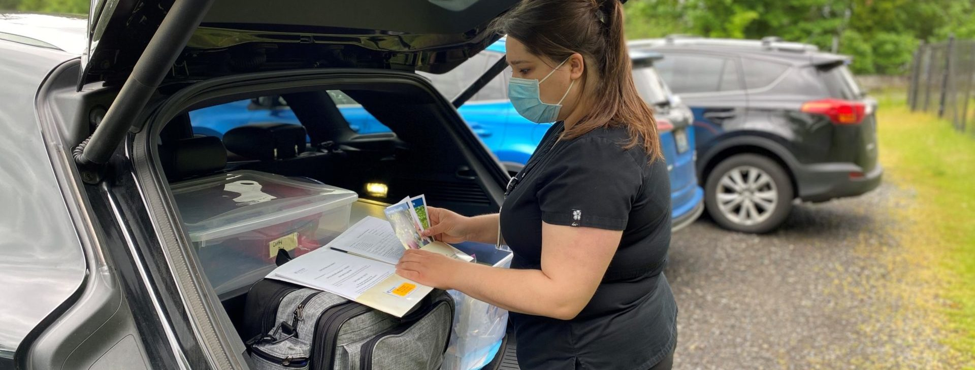Home health nurse preparing her medical supplies in the back of her SUV
