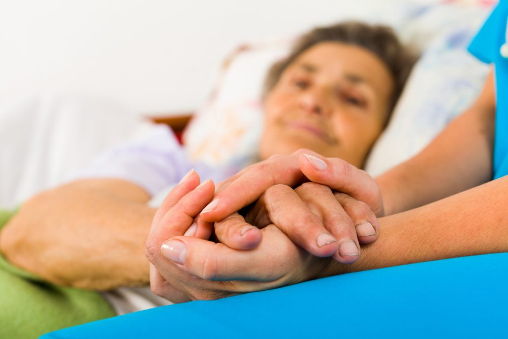 Photo of a hospice patient having her hands caressed by a family member